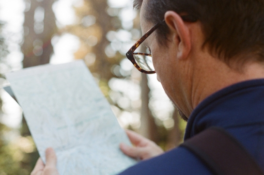 hiker with glasses reading map