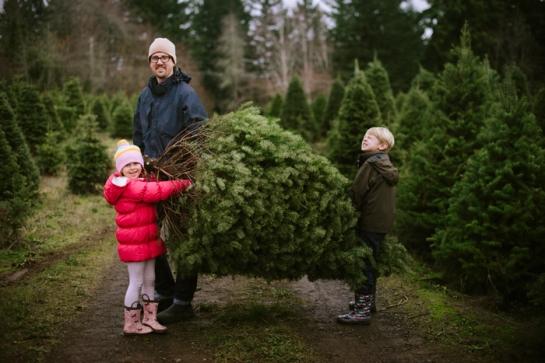 family with cut down christmas tree at xmas tree farm in oregon