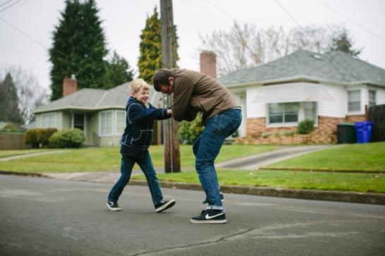 boy in street playing football with dad in portland oregon
