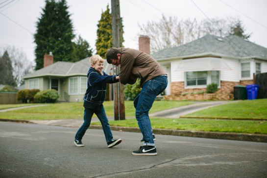 boy in street playing football with dad in portland oregon