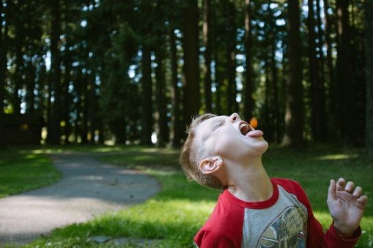boy catching food in his mouth in portland park
